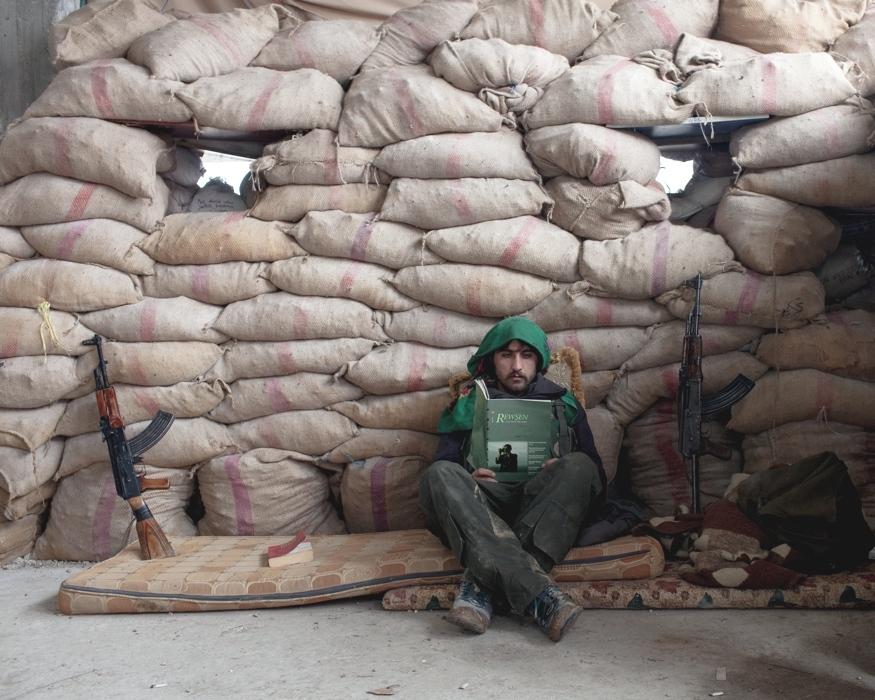Un combattente YPG legge un libro protetto dai sacchi di sabbia nella città di Kobane